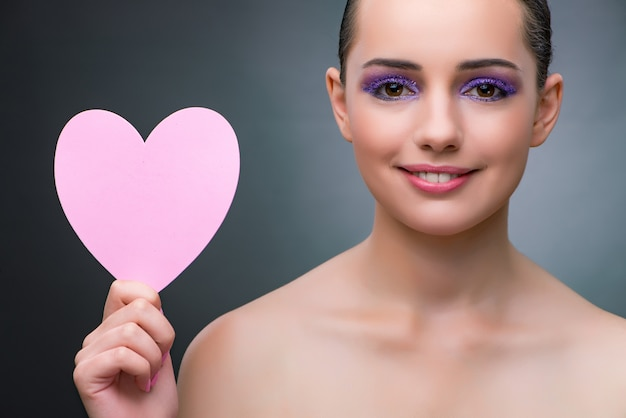 Young woman with heart shape for your message