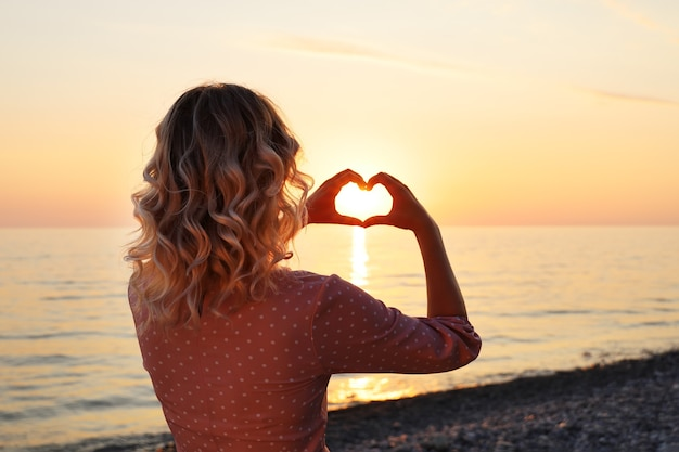 Young woman with heart-shaped fingers stands with her back on the seashore at sunset