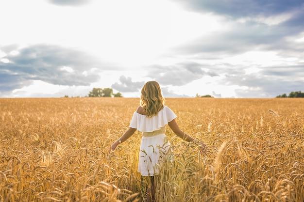 팔을 벌리고 있는 젊은 여성이 화창한 여름날, 뒷모습을 즐기고 있습니다.
