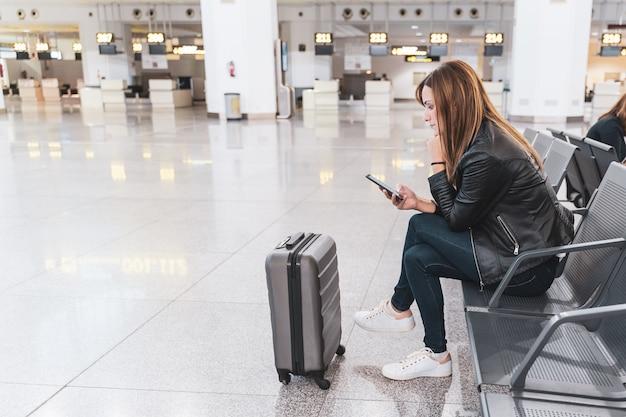 彼女の荷物と空港で待っている携帯電話を持つ若い女性。旅行と休暇の概念。