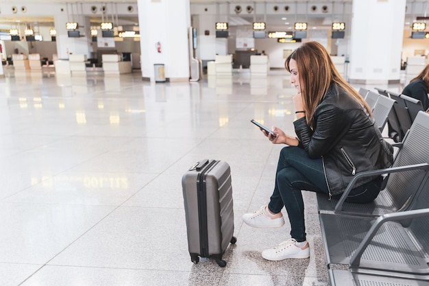Young woman with her baggage and mobile phone waiting at the airport. concept of travel and vacation.