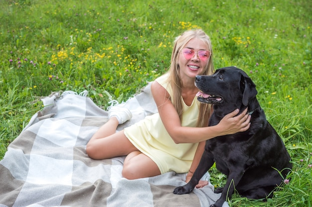 Young woman with her big black dog is sitting on a blanket on the grass in an embrace. portrait of blonde woman in pink glasses and dog