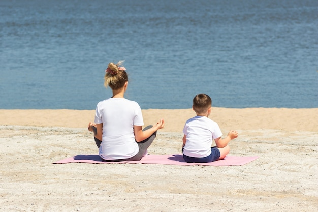 A young woman with her child in white tshirts meditate holding fingers in yoga pink mat by the sea