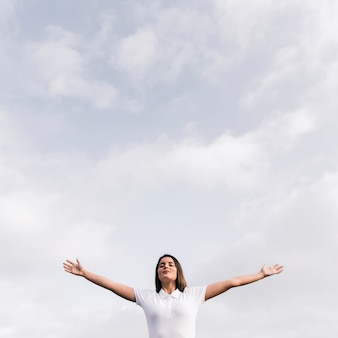 Young woman with her closed eyes outstretching her hands against blue sky