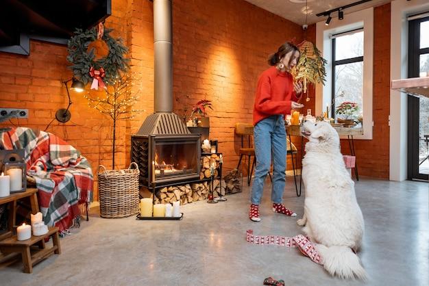 自宅の暖炉のそばで幸せな新年の休暇中に彼女のかわいい白い犬と若い女性