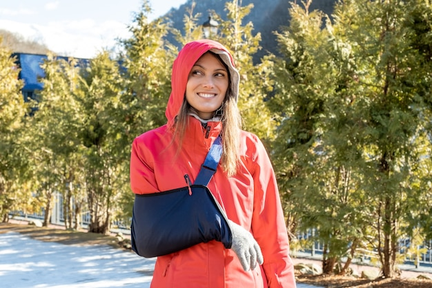 Young woman with her damaged right arm after snowboard riding