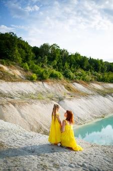 푸른 물과 푸른 나무가 있는 호수 근처에 노란 드레스를 입은 딸과 함께 젊은 여자. 행복한 가족 관계 개념