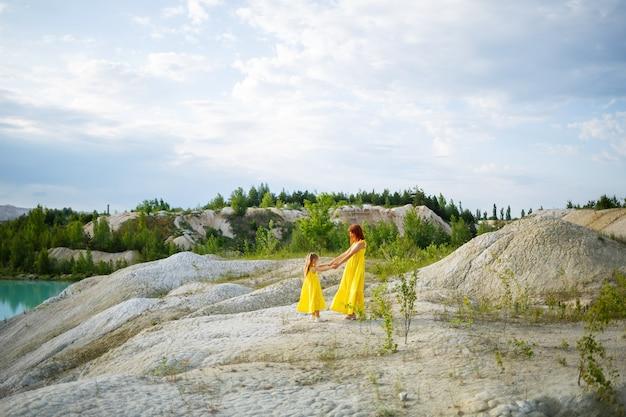 紺碧の水と緑の木々と湖の近くの黄色のドレスを着た娘と若い女性。幸せな家族関係の概念