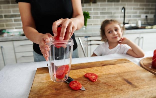 娘と一緒に若い女性がキッチンで食事を準備し、刻んだトマトのスライスを透明なブレンダーボウルに入れてさらに刻みます