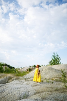 Young woman with her daughter in a yellow dress near the lake with azure water and green trees. happy family relationship concept