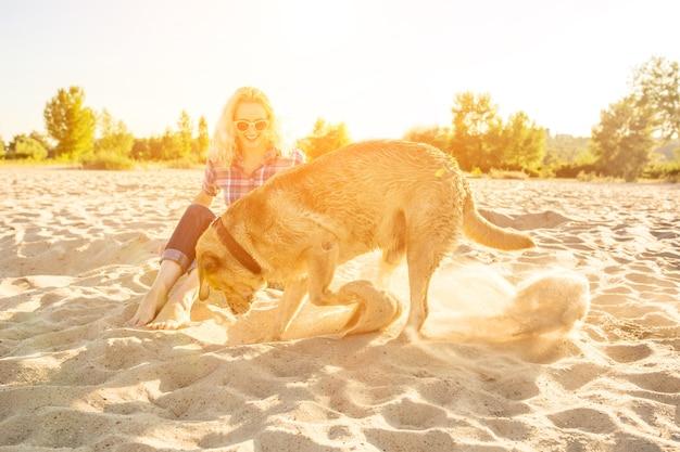 ビーチの太陽フレアで彼女の犬と若い女性