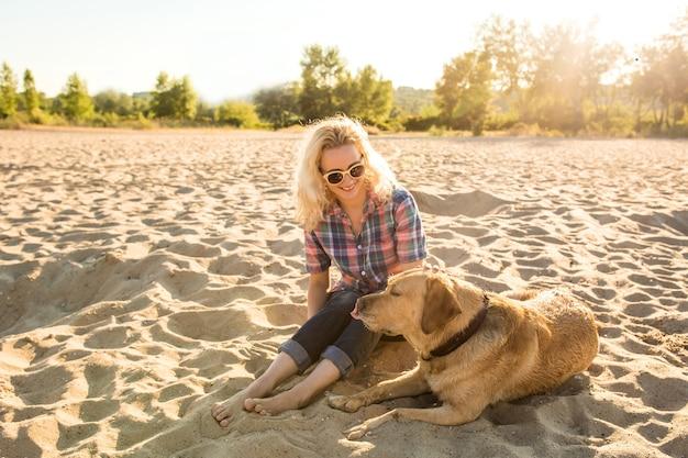ビーチで彼女の犬と若い女性