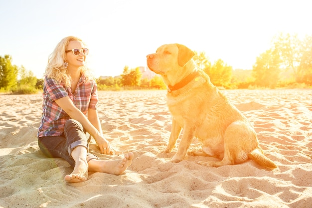 Young woman with her dog at the beach sun flare
