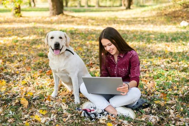 公園で彼女の犬を持つ若い女性