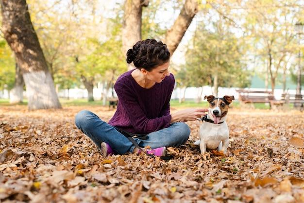 Молодая женщина с ее собакой в парке