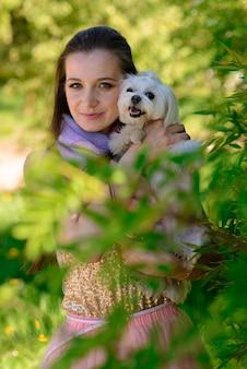 彼女の犬と若い女性。子犬の白い犬が飼い主と一緒に走っています。友情と動物についての概念。