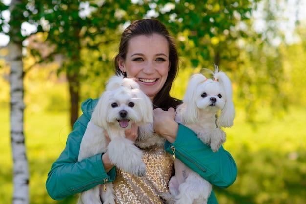 Молодая женщина со своей собакой. щенок белой собаки бежит со своим хозяином. понятие о дружбе, животном и свободе.