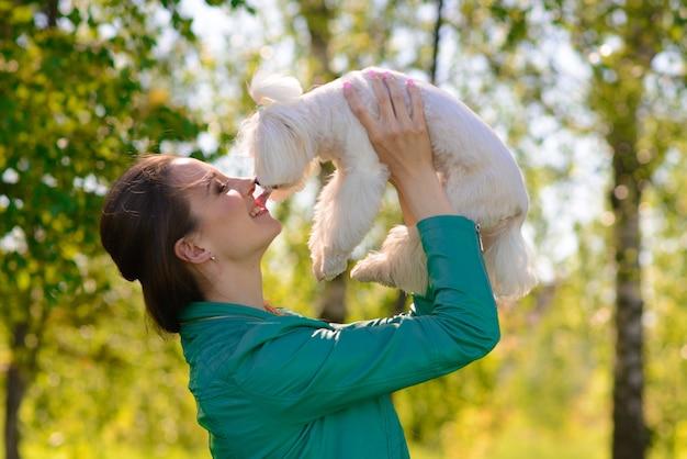 그녀의 강아지와 함께 젊은 여성. 강아지 흰 개가 주인과 함께 달리고 있습니다. 우정, 동물 및 자유에 대한 개념.