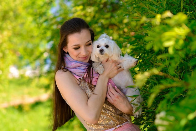 Young woman with her dog. puppy white dog is running with it's owner. concept about friendship, animal and freedom.