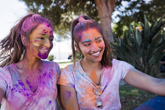 Young woman with her friend covered in holi powder taking selfie on mobile