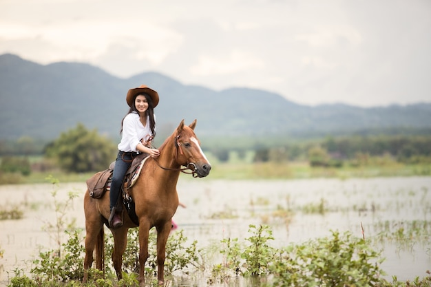 Young woman with her horse in evening sunset light. outdoor
