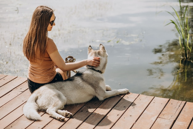 Young woman with her husky dog by the lake
