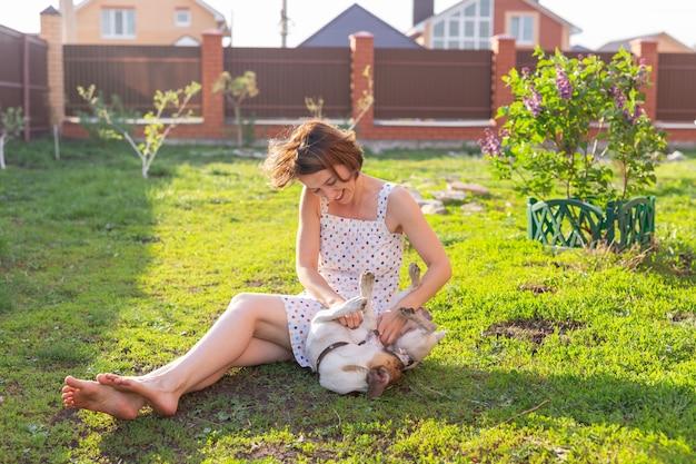 Молодая женщина со своей собакой джек-рассел-терьер играет на траве снаружи