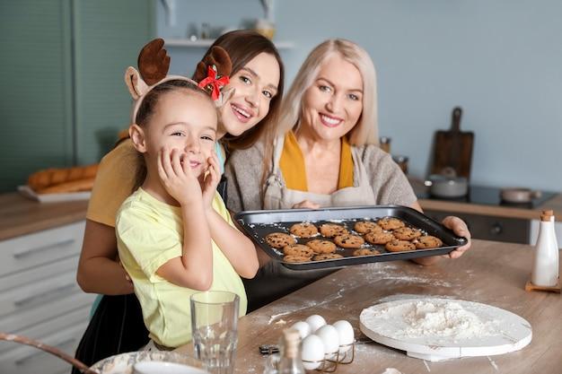 Молодая женщина с маленькой дочерью и матерью готовит рождественское печенье дома
