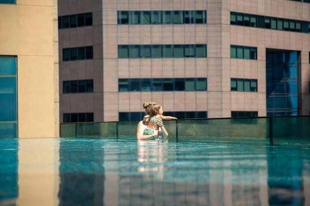 大都市の外観の超高層ビルの屋根の上のプールで彼女の小さな娘と若い女性
