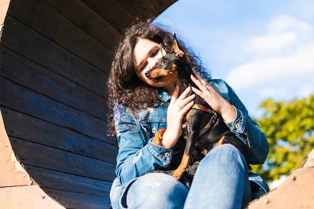 彼女の小さな犬と屋外で若い女性。公園で飼い主と黒と黄褐色のミニチュアピンシャー雌犬