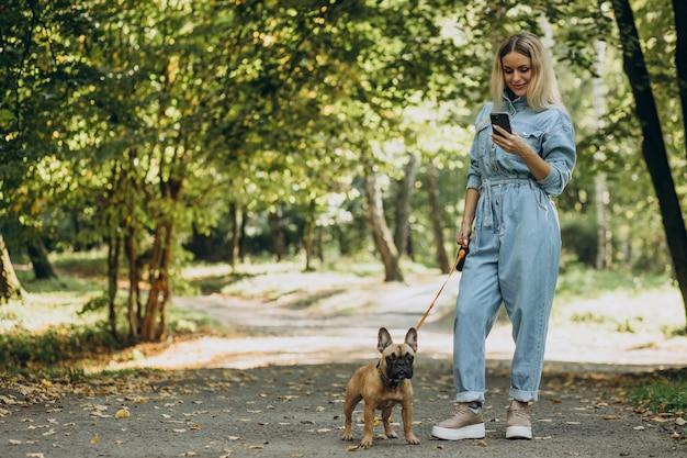 公園で彼女のペットのフレンチブルドッグと若い女性