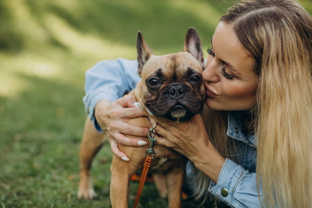 Young woman with her pet french bulldog in park