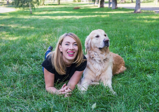 Young woman with her retriever lie on the grass in the park