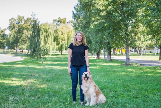 Young woman with her retriever in the park.