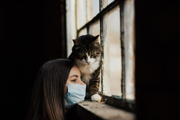 Young woman with her sad cat, sitting at home during coronavirus quarantine.