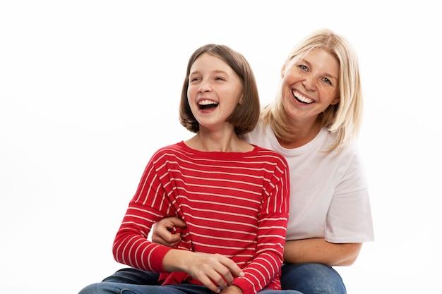 Молодая женщина с ее дочь-подросток обнимаются и смеются. белая стена.