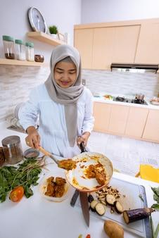 Молодая женщина с хиджабом готовит в своем доме с современной кухней на ужин