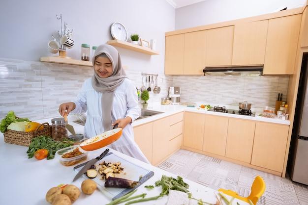 夕食のためのモダンなキッチンと彼女の家でヒジャーブ料理をしている若い女性