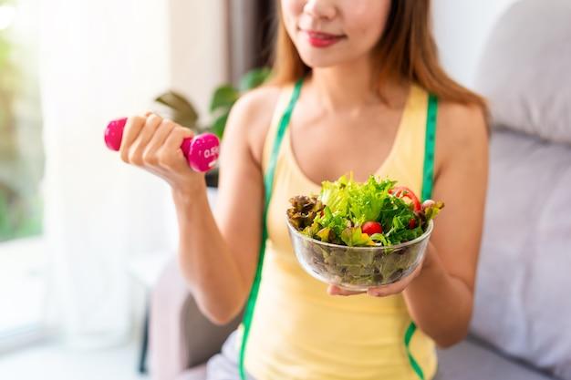 집에서 아령으로 운동하는 수제 건강 샐러드와 젊은 여자 건강한 식생활 라이프 스타일과 다이어트 개념
