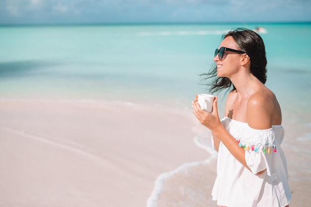 Young woman with hot coffee enjoying beach view