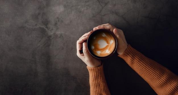 手でホットコーヒーカフェラテカップを持つ若い女性。上面図