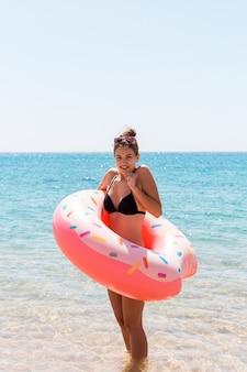 海の水に立っている膨脹可能なリング冷たい震え悲しい交差した腕の黒いビキニ水着を持つ若い女性。夏休みと休暇の概念。