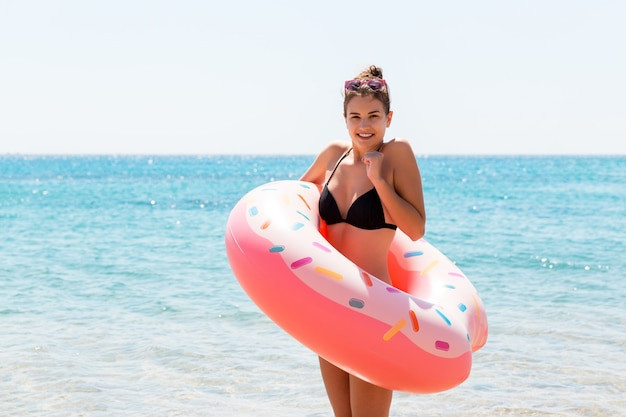 Young woman with inflatable ring cold shivering sad crossed arms black bikini swimsuit standing in sea water. summer holidays and vacation concept.