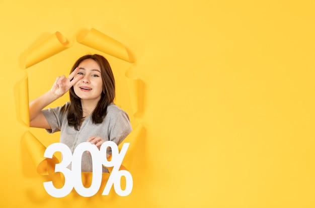 찢어진 노란 종이 배경 쇼핑 돈 판매에 비문 기호로 젊은 여자