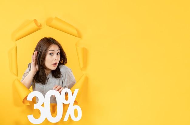 노란색 종이 배경 쇼핑 판매에 비문 기호가 있는 젊은 여성