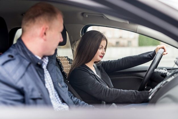 Young woman with instructor sitting in car