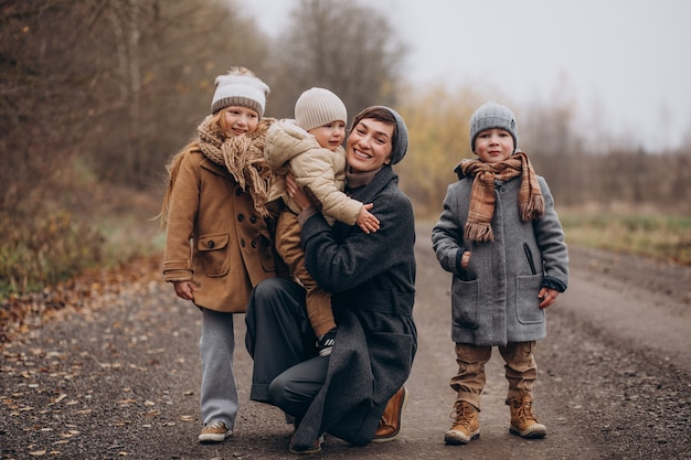 Молодая женщина с детьми гуляет в осеннем парке