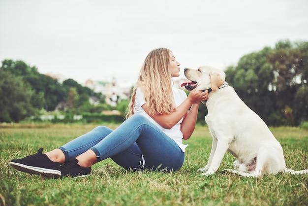 屋外でラブラドールと若い女性。犬のラブラドールレトリバーと緑の芝生の上の女性。