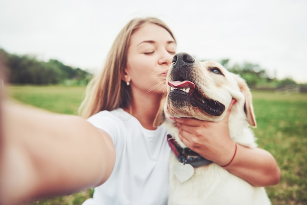 래브라도 야외에서 젊은 여자. 강아지 래브라도 리트리버와 푸른 잔디에 여자.