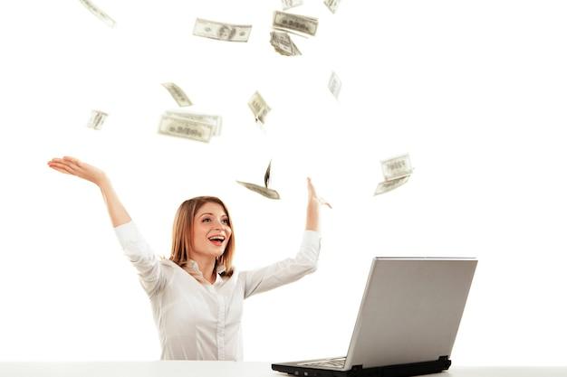 ノートパソコンと飛銭のお金を持つ若い女性。白い背景の上に分離。